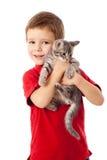 Petit garçon avec le minou gris dans des mains Image libre de droits