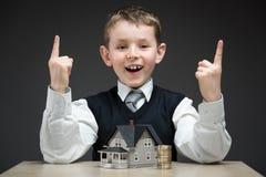 Petit garçon avec le modèle de maison et la pile des pièces de monnaie image libre de droits