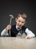 Petit garçon avec le modèle et le marteau de maison photographie stock libre de droits