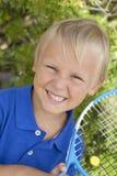Petit garçon avec le raket de tennis Photographie stock