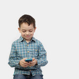 Petit garçon avec le téléphone intelligent sur le gris Photos libres de droits