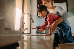 Petit garçon avec les mains de lavage de mère dans l'évier de cuisine photos stock