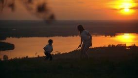 Petit garçon avec sa soeur plus âgée jouant le badminton sur la colline au coucher du soleil banque de vidéos