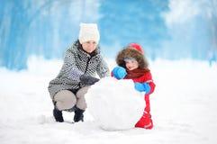 Petit garçon avec son bonhomme de neige de bâtiment de mère/babysitter/grand-mère en parc neigeux Photographie stock