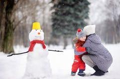 Petit garçon avec son bonhomme de neige de bâtiment de mère/babysitter/grand-mère en parc neigeux Photos stock