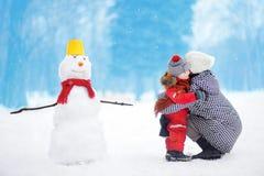 Petit garçon avec son bonhomme de neige de bâtiment de mère/babysitter/grand-mère en parc neigeux Photos libres de droits