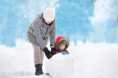 Petit garçon avec son bonhomme de neige de bâtiment de mère/babysitter/grand-mère en parc neigeux Image stock