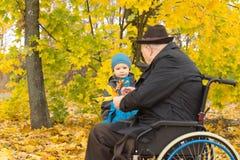 Petit garçon avec son grand-père handicapé Image stock