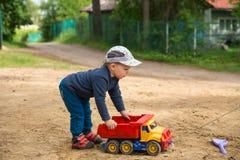 Petit garçon avec un camion en plastique Image libre de droits