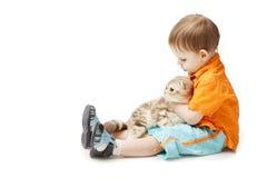 Petit garçon avec un chat sur un fond blanc Photographie stock libre de droits