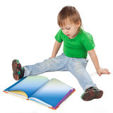 Petit garçon avec un livre se reposant sur le plancher Photo libre de droits