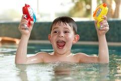 Petit garçon ayant l'amusement avec des pistolets d'eau Photo libre de droits