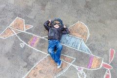 Petit garçon ayant l'amusement avec le dessin de photo d'avion avec la craie Photos stock
