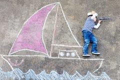 Petit garçon ayant l'amusement avec le dessin de photo de bateau Photographie stock libre de droits