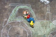 Petit garçon ayant l'amusement avec le dessin de photo de tracteur avec la craie images libres de droits