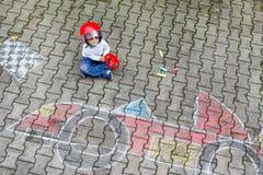 Petit garçon ayant l'amusement avec le dessin de voiture de course avec des craies Photo libre de droits