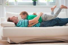 Petit garçon ayant l'amusement avec le père à la maison Photo stock