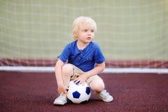 Petit garçon ayant l'amusement jouant un football/partie de football le jour d'été Photographie stock