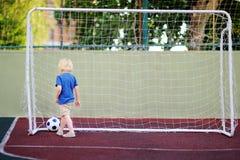 Petit garçon ayant l'amusement jouant un football/partie de football le jour d'été Image stock