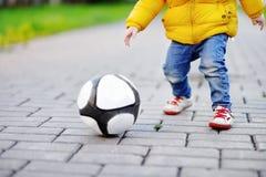 Petit garçon ayant l'amusement jouant un jeu de football le jour ensoleillé de printemps ou d'automne Photo stock