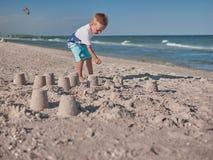 Petit garçon ayant sur l'amusement de plage avec le sable Bébé jouant sur le bord de la mer dans les summertimes Concept de repos photos libres de droits
