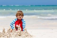 Petit garçon blond adorable d'enfant ayant l'amusement sur la plage tropicale de l'île carribean Sable de jeu et de construction  image libre de droits