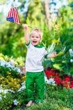 Petit garçon blond aux pieds nus riant et ondulant le drapeau américain Photographie stock