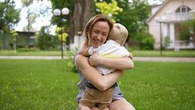 Petit garçon blond courant à sa mère La maman a ouvert ses mains et le sourire attrape le bébé Mère heureuse, fils affectueux banque de vidéos