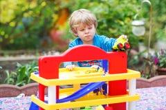 Petit garçon blond d'enfant en bas âge jouant avec le jouet - station de parking dedans Photo libre de droits