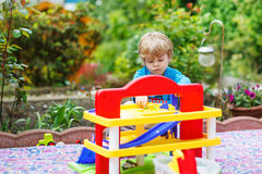 Petit garçon blond d'enfant en bas âge jouant avec le jouet - station de parking dedans Image libre de droits