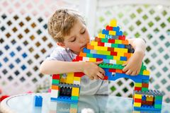 Petit garçon blond d'enfant et d'enfant jouant avec un bon nombre de blocs en plastique colorés Photo stock