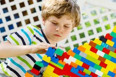 Petit garçon blond d'enfant et d'enfant jouant avec un bon nombre de blocs en plastique colorés Photo libre de droits