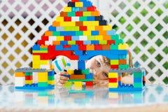 Petit garçon blond d'enfant et d'enfant jouant avec un bon nombre de blocs en plastique colorés Photographie stock libre de droits
