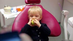 Petit garçon blond dans la chaise dentaire mangeant une pomme verte banque de vidéos