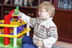 Petit garçon blond de trois ans jouant avec des jouets à la maison Photographie stock