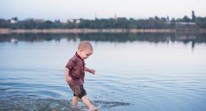Petit garçon blond drôle éclaboussant en belle rivière la journée de printemps photos stock