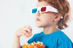Petit garçon blond en verres 3D avec le bol de maïs éclaté Photographie stock libre de droits