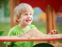 Petit garçon blond jouant sur le terrain de jeu Photos stock