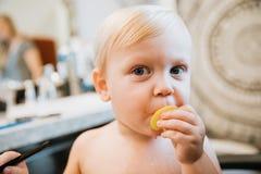 Petit garçon blond mignon adorable précieux d'enfant en bas âge montrant sa nouvelle coiffure après l'obtention de sa première co photo libre de droits