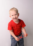 Petit garçon blond riant dans la chemise rouge photo stock