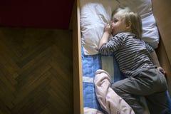 Petit garçon blond songeur mignon se situant dans le lit photographie stock