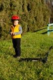 Petit garçon boudeur regardant son scooter Image stock