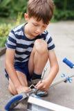 Petit garçon caucasien réparant le scooter Photos stock