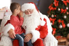 Petit garçon chuchotant dans l'oreille authentique de ` de Santa Claus à l'intérieur photos stock