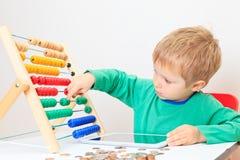 Petit garçon comptant son épargne Image libre de droits