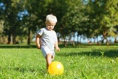 Petit garçon concentré donnant un coup de pied une boule dans le jardin photo libre de droits