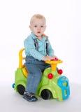 Petit garçon conduisant sur la voiture de jouet photos stock