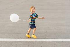 Petit garçon courant avec un ballon Images libres de droits