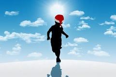 Petit garçon courant dans le chapeau rouge sur le fond d'hiver Image libre de droits