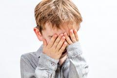Petit garçon couvrant son visage pour jouer le coup d'oeil ou la disparition Images libres de droits